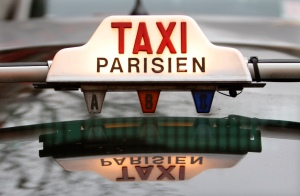 The top of a taxi is seen in downtown Paris. By Jean Piere Gallot.