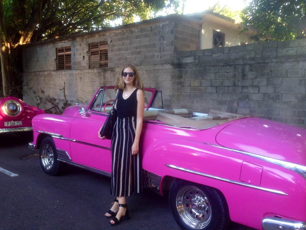 Elizabeth Kester with pink car in Cuba