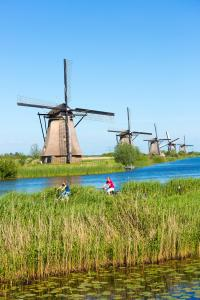 Cyclists pass group of authentic windmills at Kinderdijk UNESCO World Heritage Site, dykes and polder, Holland, The Netherlands